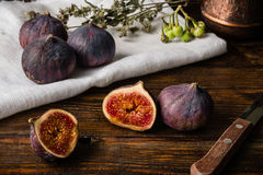 Ripe figs on cloth with sliced one and some objects. Ripe seasonal figs on the cloth and wooden surface with sliced one and some objects Stock Image