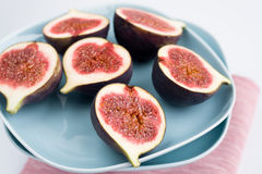 Ripe figs lying on a blue plate on pink napkin Royalty Free Stock Photos