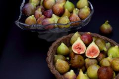 Ripe figs in a wicker basket on dark background. Some whole figs in a glass bowl Royalty Free Stock Photo