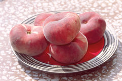 Ripe flat peaches on a plate Stock Photo
