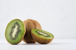 Ripe fleshy green kiwi group with juicy slices on soft light white table. Ripe fleshy green kiwi group with juicy slices on soft light white table stock photography