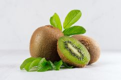 Ripe fleshy green kiwi with juicy slice, young leaves on soft light white table, closeup. Tropical fruits background stock photo
