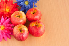 Ripe four red apple with artificial flower Royalty Free Stock Photography