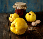 Ripe fragrant quince, jam, walnuts on a wooden background. Ripe quince, jam, walnuts on a wooden background Stock Photography