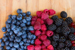 Ripe  of fresh berries on table. Ripe of fresh raspberry, blackberry and blue berry  on wooden table Stock Images
