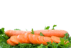Ripe fresh carrot and slices over some parsley. Ripe fresh long carrot and slices over some parsley isolated on the white background (focused on carrot slices Stock Image