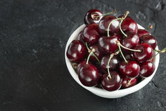 Ripe fresh cherries in a white plate. Ripe cherry berries in white plate on concrete background Stock Image