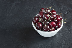 Ripe fresh cherries in a white plate on a dark background. Ripe cherry berries in white plate on concrete background Stock Photo