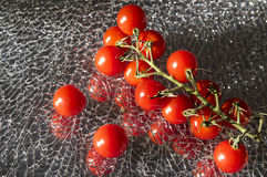 Ripe Fresh Cherry Tomatoes on Broken Mirror Glass. Ripe Fresh Cherry Tomatoes Branch on Broken Mirror Glass royalty free stock images