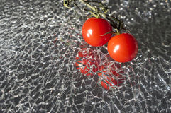 Ripe Fresh Cherry Tomatoes on Broken Mirror Glass. Couple of Ripe Fresh Cherry Tomatoes on Broken Mirror Glass stock photos