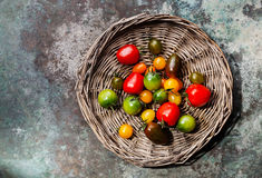 Ripe fresh colorful tomatoes on wicker tray Stock Image