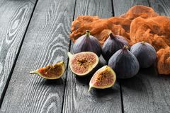 Ripe fresh figs on dark wooden background. Whole fruits, half and slices. Source of potassium, calcium, phosphorus, vitamins B, PP, A, C. Contains substances Stock Photos