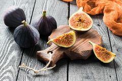 Ripe fresh figs on dark wooden background. Whole fruits, half and slices. Source of potassium, calcium, phosphorus, vitamins B, PP, A, C. Contains substances Stock Photo