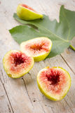 Ripe fresh figs. Some slices of ripe figs on wooden background Stock Photography