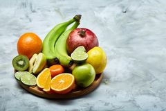 Ripe fresh fruits in a wooden plate on a light background, selective focus, close-up, top view Royalty Free Stock Photography