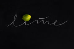 Ripe fresh lime with the inscription. Over black background Royalty Free Stock Photos