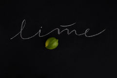 Ripe fresh lime with the inscription. Over black background Stock Photography
