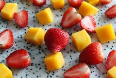 Ripe and fresh mango, dragon fruit and strawberries close up. Royalty Free Stock Photo