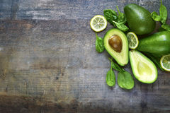 Ripe fresh organic avocado with spinach leaves and lemon slices. Stock Photos