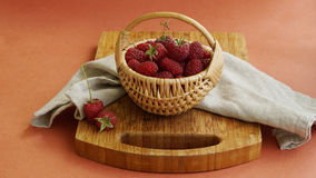 Rasberry in basket. Ripe fresh organic rasberry in little basket on wooden desk on red background Royalty Free Stock Image
