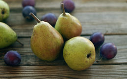 Ripe fresh pears and plums. On a wooden background close up. Autumn harvest of fruit Royalty Free Stock Images