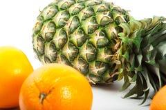 Ripe fresh pineapple and orange  on white background Stock Image