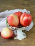 Ripe fresh pink peaches in vase Stock Photo