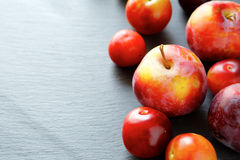 Ripe fresh plums on a stone plate Stock Photo