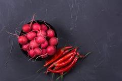Ripe fresh radish. With spicy chili pepper on dark background Stock Photo