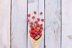 Ripe fresh raspberries in ice cream cone on rustic wooden background. Stylish flat lay. Minimal concept Stock Image