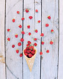 Ripe fresh raspberries in ice cream cone on rustic wooden background. Stylish flat lay. Minimal concept Stock Photos