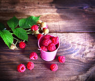 Ripe fresh raspberries in a pink iron bucket. On a brown wooden table, top view Stock Image