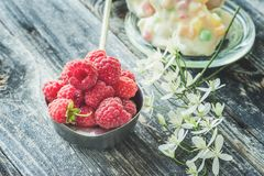 Ripe fresh raspberries in a white pot in a rustic style with small white clematis flowers close-up. Copy space Stock Photo