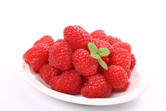 Ripe fresh raspberry with mint on plate over white.  Stock Photo
