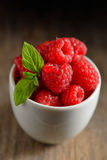 Ripe and fresh raspberry in white cup. On wooden table Royalty Free Stock Photography