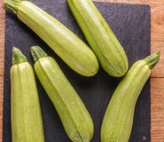Ripe  fresh raw courgettes on black background. Ripe  green fresh raw zucchini, for cooking, on black background Royalty Free Stock Photos