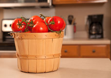 Basket of tomatoes on kitchen counter. Ripe, fresh, red tomatoes in wicker basket sitting on kitchen counter royalty free stock photography