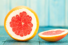 Ripe fresh sliced grapefruit on a blue wooden background. Diet, vegetarianism Royalty Free Stock Image