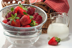 Ripe fresh strawberries in a colander and milk cream in a jug. Ripe fresh strawberries in a colander and milk cream in a glass jug Stock Image