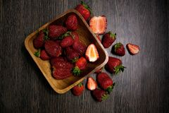 Ripe fresh strawberries in a wooden bowl on a dark background. Eco products. Healthy food. Good for illustrating vegetarianism, ra. Ripe fresh strawberries in a Royalty Free Stock Photo