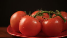 Ripe fresh tomatoes branch lies on red plate on the table stock video