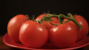 Ripe fresh tomatoes branch lies on red plate on the table stock footage