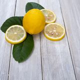 Ripe fresh whole lemons in wicker basket. Lemon cut and green leaf on white table, space for your text stock images