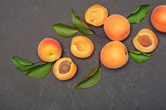 Ripe fruit for healthy life. Fresh apricot with green leaves. On black background stock images