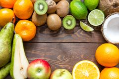 Ripe fruit pear kiwi lime coconut apple orange mandarin lie in a circle on a wooden table in the center of the place for. Ripe juicy fruit pear kiwi orange Stock Photos