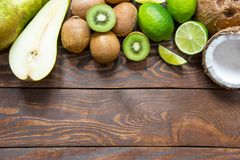 Ripe fruit pear kiwi lime coconut on a wooden table top with a place for inscription. Ripe fruit pears kiwi lime and coconut on a brown wooden table have a place Stock Photo