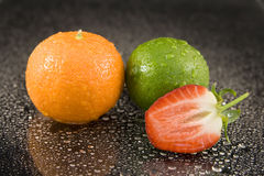 Ripe fruit on water. Ripe whole orange and lime with halved strawberry on drops of water Royalty Free Stock Photo