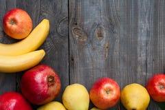 Ripe fruit on wooden background: banana, apple, pear and pomegra Stock Image