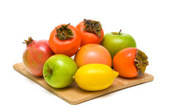 Ripe fruit on a wooden cutting board closeup on white background Stock Photography