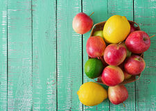 Ripe fruits (apples, lemons and limes) on a bright wooden background. Stock Photo